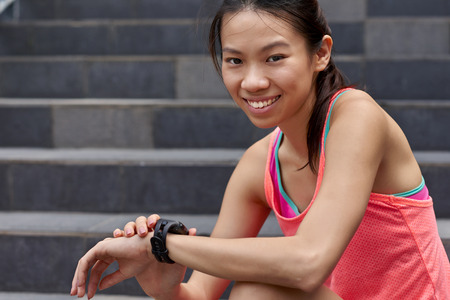 rate: portrait of sporty asian chinese woman sitting outdoors checking workout time on wearable technology watch after run