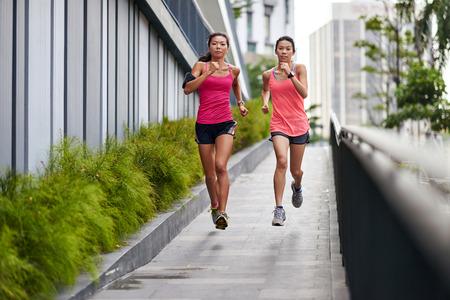 朝のトレーニングのアウトドアで下り坂のランニング スポーティなアジア中国女性