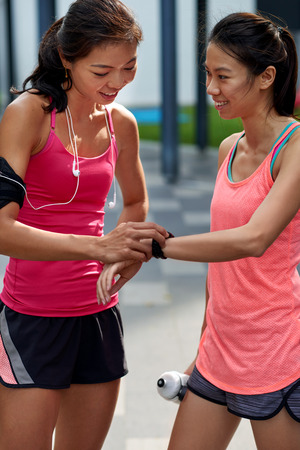 rate: asian chinese fitness women friends checking training running time on wearable technology watch outdoors Stock Photo