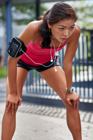 overheating: exhausted sporty asian chinese woman runner after fitness running workout outdoors Stock Photo