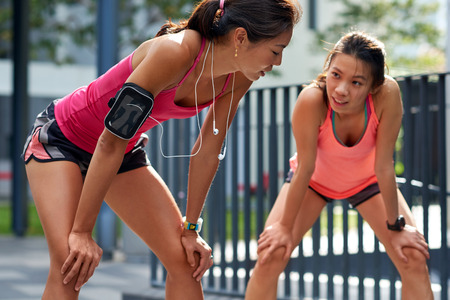 overheating: exhausted sporty asian chinese women runners after fitness running workout outdoors