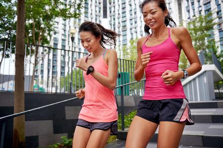 朝のトレーニングの屋外階段を下りて走ってアジア中国スポーティな女性