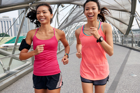 cardio fitness: asian chinese happy women enjoying a run together for morning outdoor workout