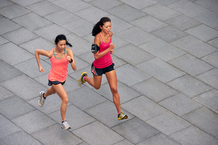 朝のマラソン大会に備えてトレーニング屋外に活発なアジア中国スポーティな女性の実行します。 写真素材