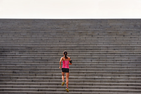 sporty woman working out running up stairs outdoors for morning workout