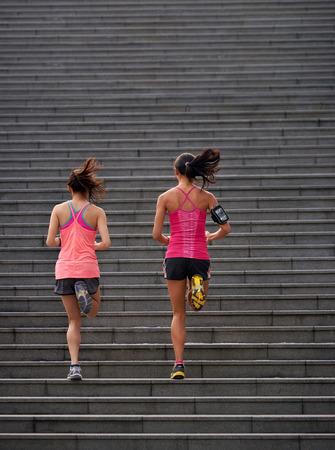 アクティブなスポーティな女性の朝の運動の屋外階段を実行してから作業