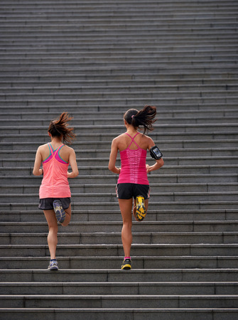 active sporty women working out running up stairs outdoors for morning workout 스톡 콘텐츠