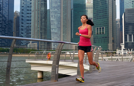 jog: asian chinese sporty woman working out running outdoors along urban city harbor sidewalk morning