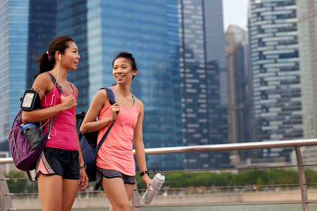 happy active sporty asian chinese women chatting outdoors near urban cityscape