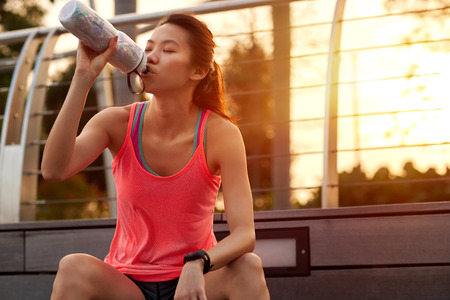 asian sport: sporty asian chinese woman sitting outdoors resting drinking water bottle after morning run