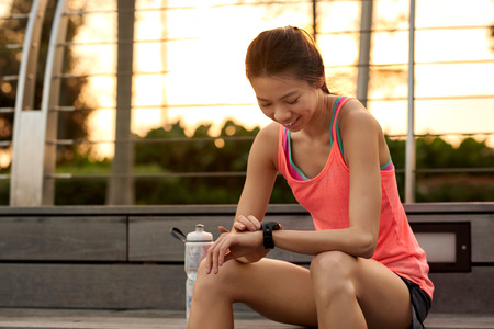 rate: sporty asian chinese woman sitting outdoors checking workout time on wearable technology watch after run