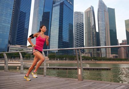 corriendo: asi�tico mujer china en marcha deportiva que se resuelve correr al aire libre a lo largo de la ciudad urbana acera puerto de ma�ana Foto de archivo