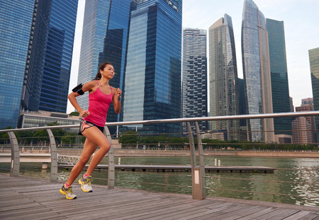 singapore city: asian chinese sporty running woman working out running outdoors along urban city harbor sidewalk morning Stock Photo