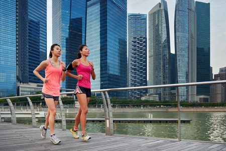asian chinese sporty running women working out jogging outdoors along urban city harbor sidewalk morning 스톡 콘텐츠