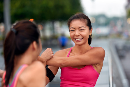 active lifestyle: happy asian chinese sporty women doing stretching exercise outdoors