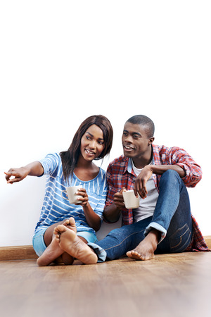 buyers: Young african couple sitting on floor of new home with coffee and being happy with life success of property investment
