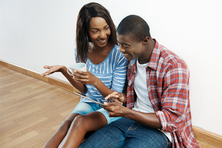 home furnishings: happy young african couple looking on tablet computer for new home furnishings for their apartment