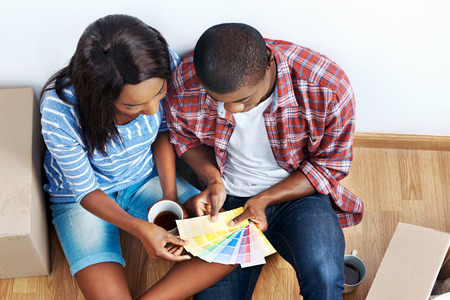 overhead view of young black african couple with moving boxes in new apartment choosing colour of paint for walls