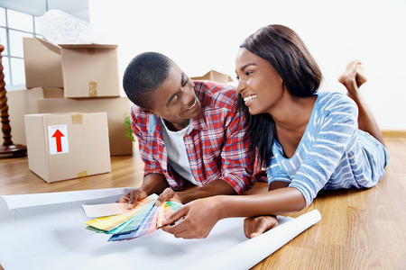 people moving: young african couple having fun deciding on paint colour swatch for new home apartment Stock Photo