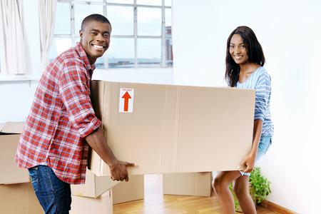 mujer enamorada: j�venes africanos par mover cajas negras en el nuevo hogar junto que hacen una vida exitosa