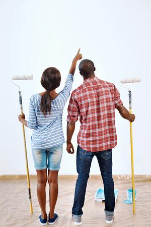 pareja en casa: Pareja joven negro listo para pintar su apartamento nuevo hogar juntos