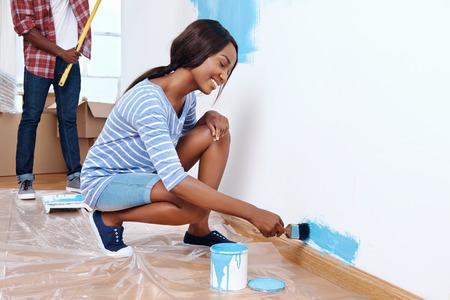 hombre pintando: Nueva capa de pintura en el nuevo apartamento para pareja joven africano negro que tienen éxito y un hogar
