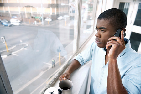 black professional: young african businessman with coffee and mobile phone at window in morning
