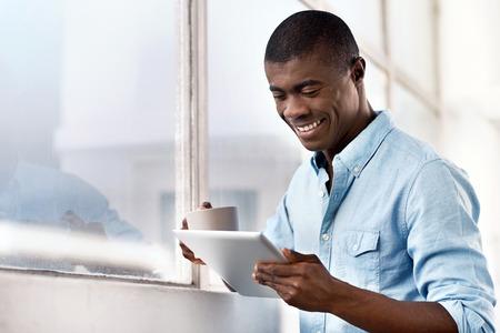 exito: hombre joven africano negro �xito con caf� de la ma�ana y el ordenador tableta de la comprobaci�n de las noticias de las inversiones Foto de archivo