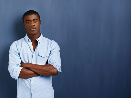 confident african man with arms crossed standing against blue wall for copyspace