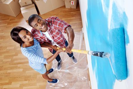 HOMBRE PINTANDO: alta vista aérea de la joven pareja pared de pintura negro con el rodillo en la nueva casa