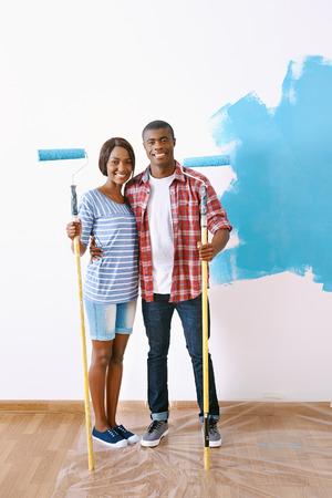 pareja en casa: Nueva capa de pintura en el nuevo apartamento para pareja joven africano negro que tienen éxito y un hogar