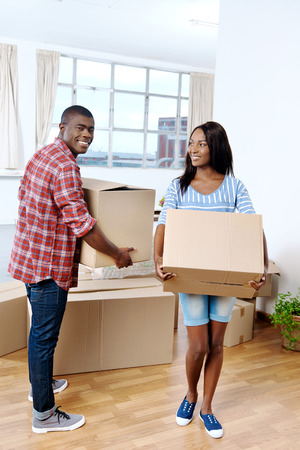 african family: young black african couple moving boxes into new home together making a successful life Stock Photo