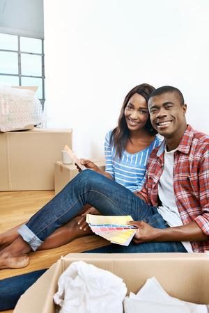 pareja hogar: joven africano pareja se divierte decidir sobre pintura muestra de color para apartamento nuevo hogar