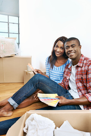 home moving: young african couple having fun deciding on paint colour swatch for new home apartment Stock Photo