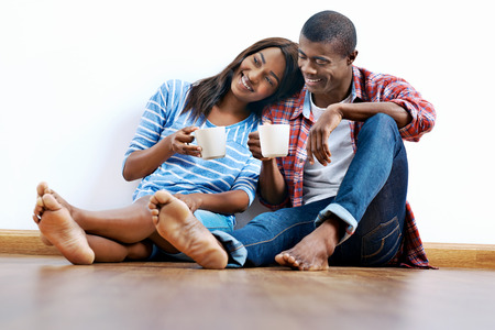 moving house: Young african couple sitting on floor of new home with coffee and being happy with life success of property investment