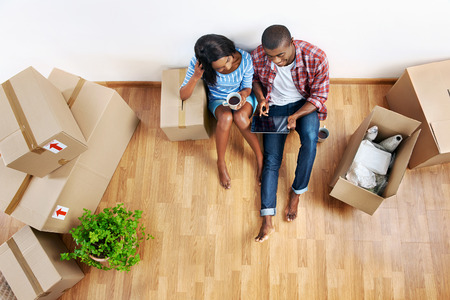 people moving: overhead view of young black african couple with moving boxes in new apartment using modern tablet computer technology