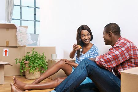 jovem casal negro que comemora seu novo apartamento e chave de passagem Imagens