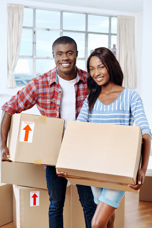 young black african couple moving boxes into new home together making a successful life 스톡 콘텐츠