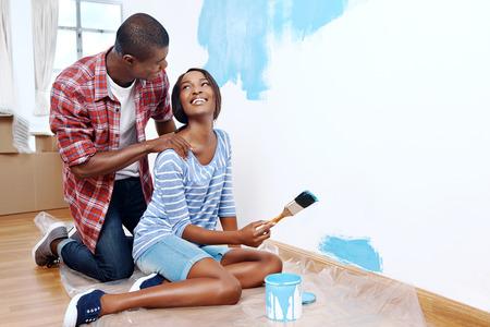 leuchtend: Frischen Anstrich auf neue Wohnung für junge schwarze afrikanische Paar, Erfolg und ein Zuhause haben