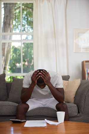 disapointed troubled african black man sitting on sofa couch calculating home bill finance debt in living room Imagens - 42071719