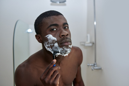 shaving cream: portrait of shirtless african black man shaving beard stubble face with razor in mirror reflection for morning clean shaven look in home bathroom