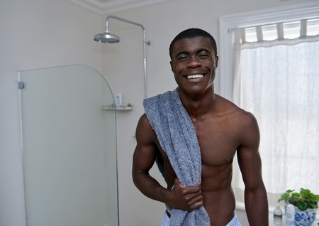 black bathroom: portrait of handsome african black man standing with towel in home bathroom