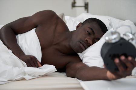 woken: african black man awake comfortably in bed woken up by alarm clock early morning