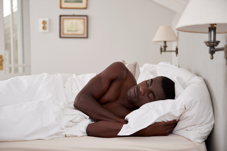 nap: peaceful african black man sleeping comfortably in bed at home Stock Photo