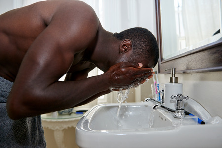 shirtless african black man washing face in basin morning in home bathroom