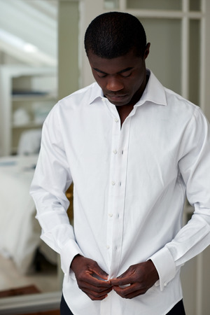 'getting ready': handsome professional african black man getting ready morning routine shirt at home for work