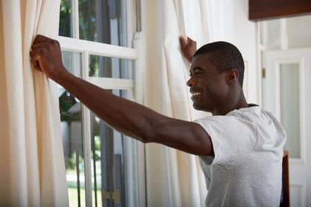 opening window: apuesto hombre africano abriendo cortinas de la ventana para la luz de la ma�ana en su casa