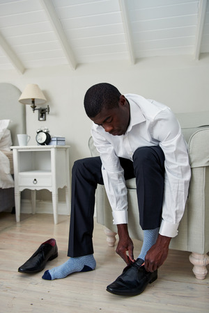 working dress: professional african black man getting ready for work putting formal smart shoes on for work in morning at home