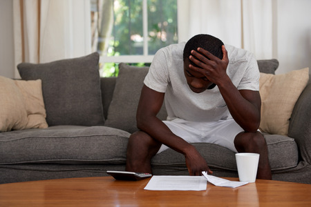 disapointed troubled african black man sitting on sofa couch calculating home bill finance debt in living room