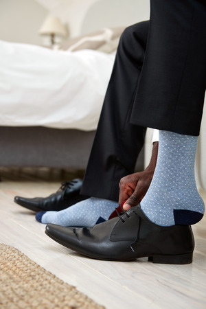 putting on: professional man getting ready for work putting formal smart shoes on for work in morning at home